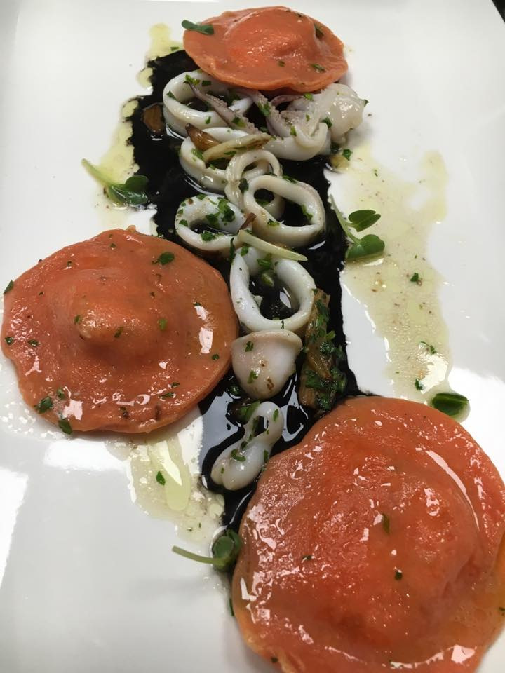 Sea Bass and potatoes filled red tomato ravioli over sautéed garlic calamari with black squid ink sauce